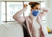 Young woman using protective face mask at home during coronavirus pandemic.