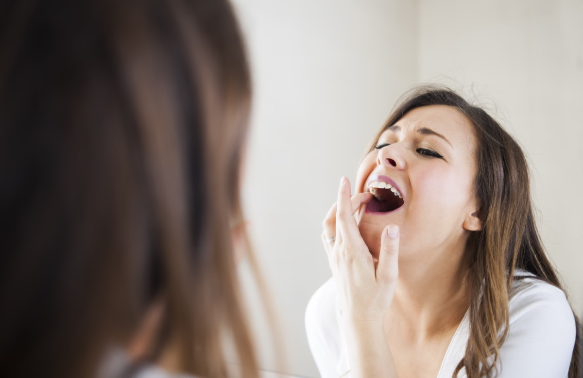 Woman looking her self in mirror, she have toothache