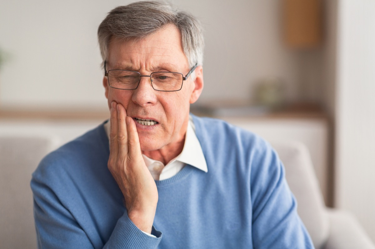 Elderly Man Having Toothache Touching Cheek Suffering From Pain Sitting On Sofa At Home. Selective Focus