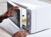 man putting food in white microwave