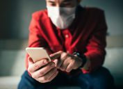 man using phone at home while wearing a mask