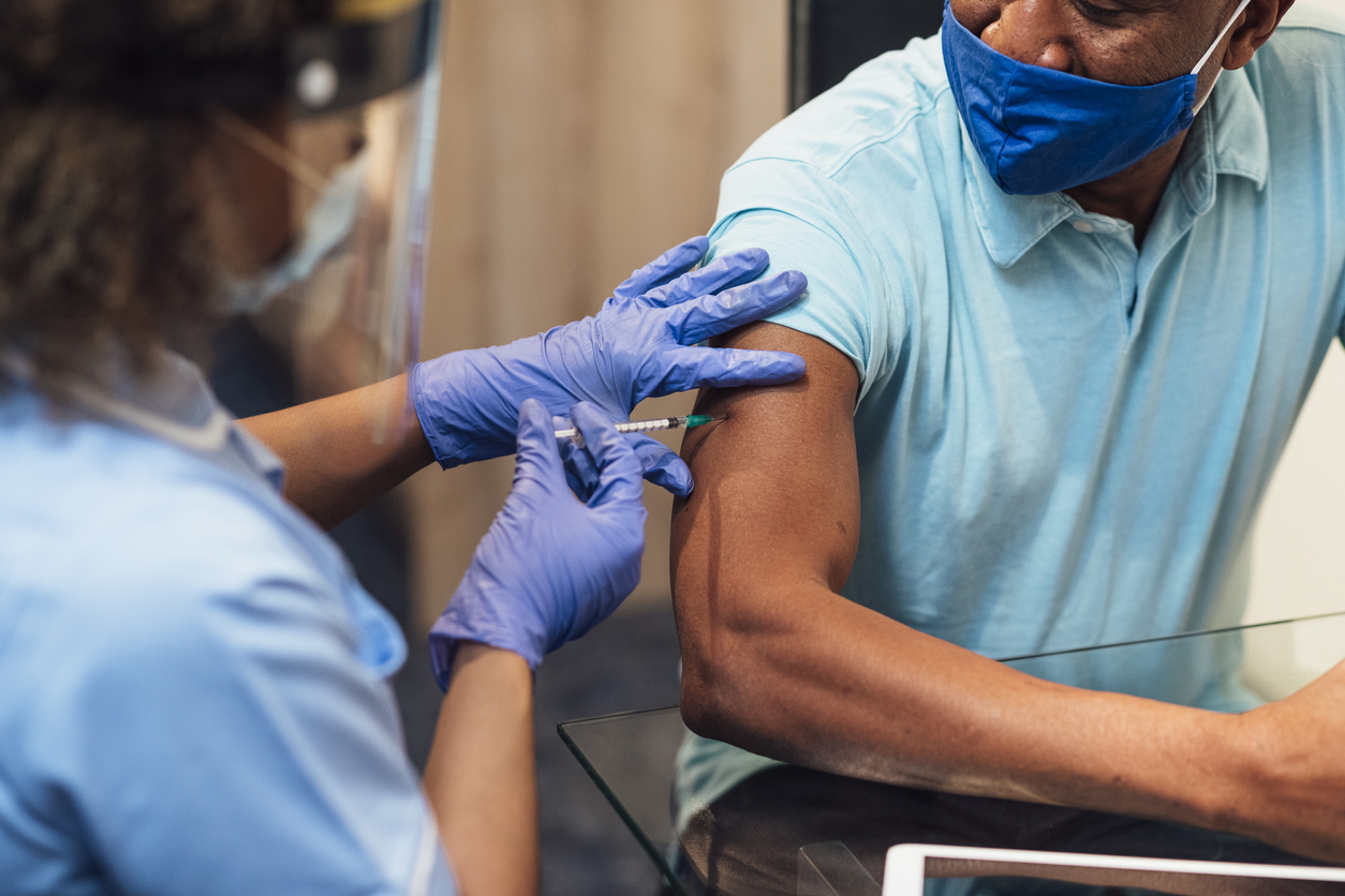 A female healthcare worker injects a middle-aged man with the COVID-19 vaccine.