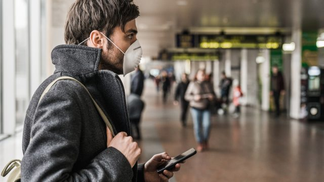 Man wearing protective mask to prevent Coronavirus and using mobile phone in airport terminal