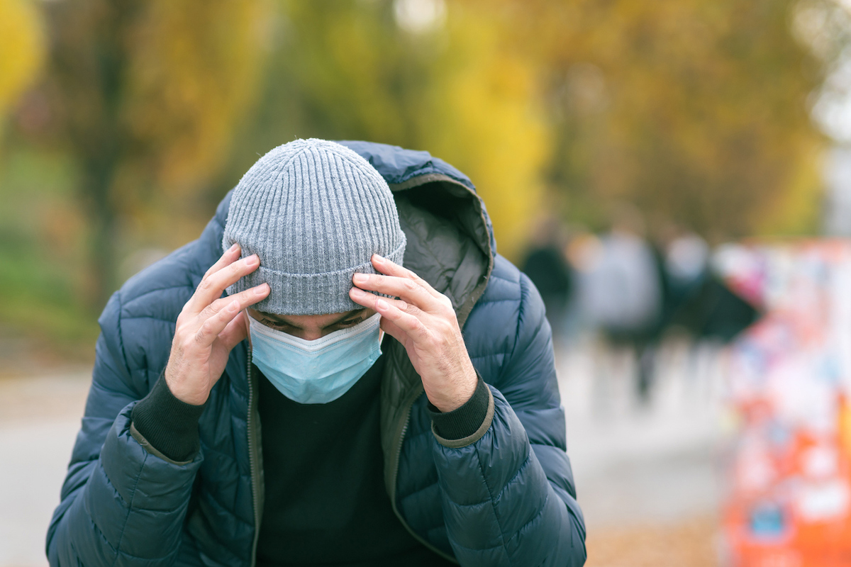 A man in a medical mask in the park with his hand on his head due to a headache.