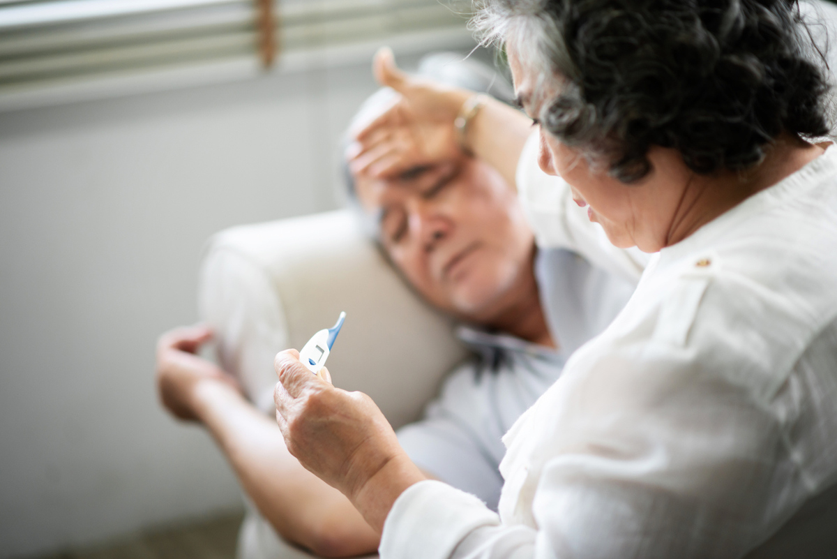 Sick senior man lying on sofa while his wife is holding and looking to thermometer