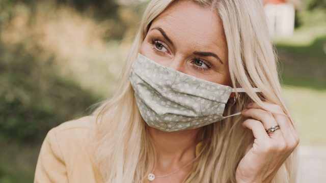 Content woman putting on wearing a protective mask in times of corona Mid adult woman earing a textiel mask with pocket for filter Photo taken outdoors in summer