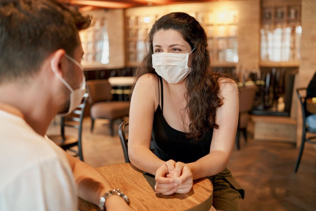 woman and man at restaurant wearing masks