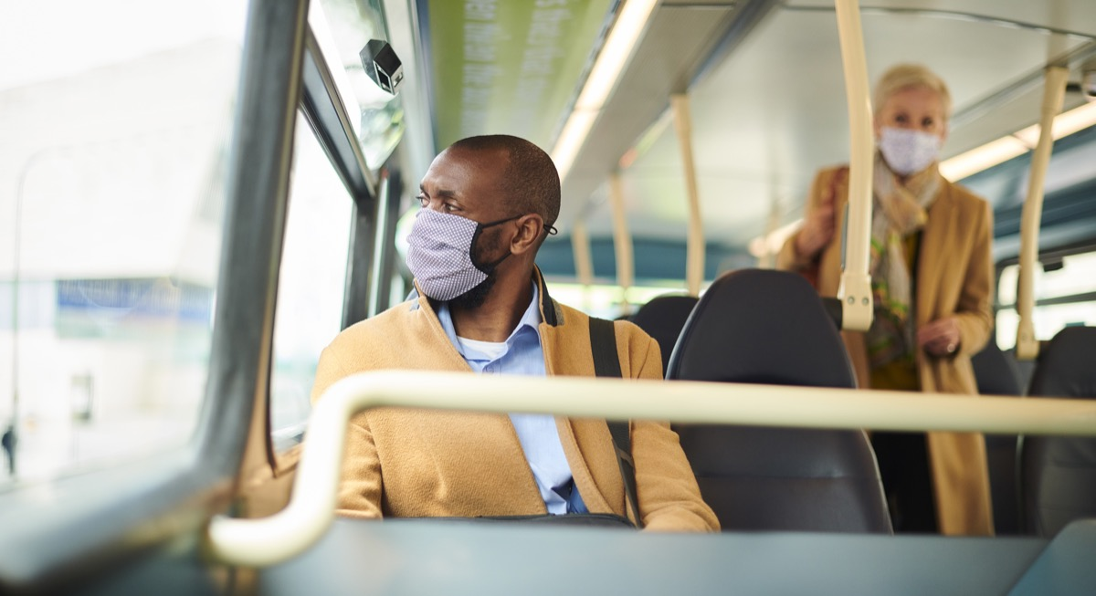 young man wearing mask on bus