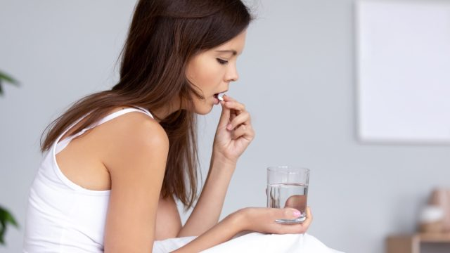 Woman taking over-the-counter medication with water