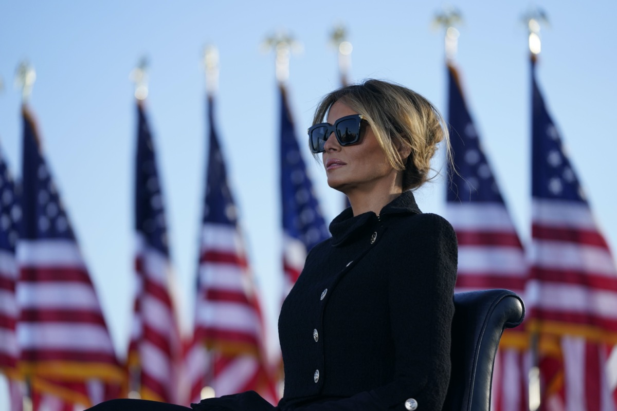 melania trump wears sunglasses while addressing the crowd in front of american flags