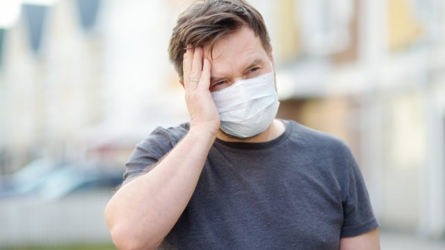 A middle-aged man wearing a face mask holds his head in pain, perhaps with symptoms of COVID-19.