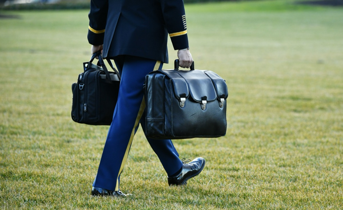 a uniformed member of the armed services brings the nuclear football to marine one