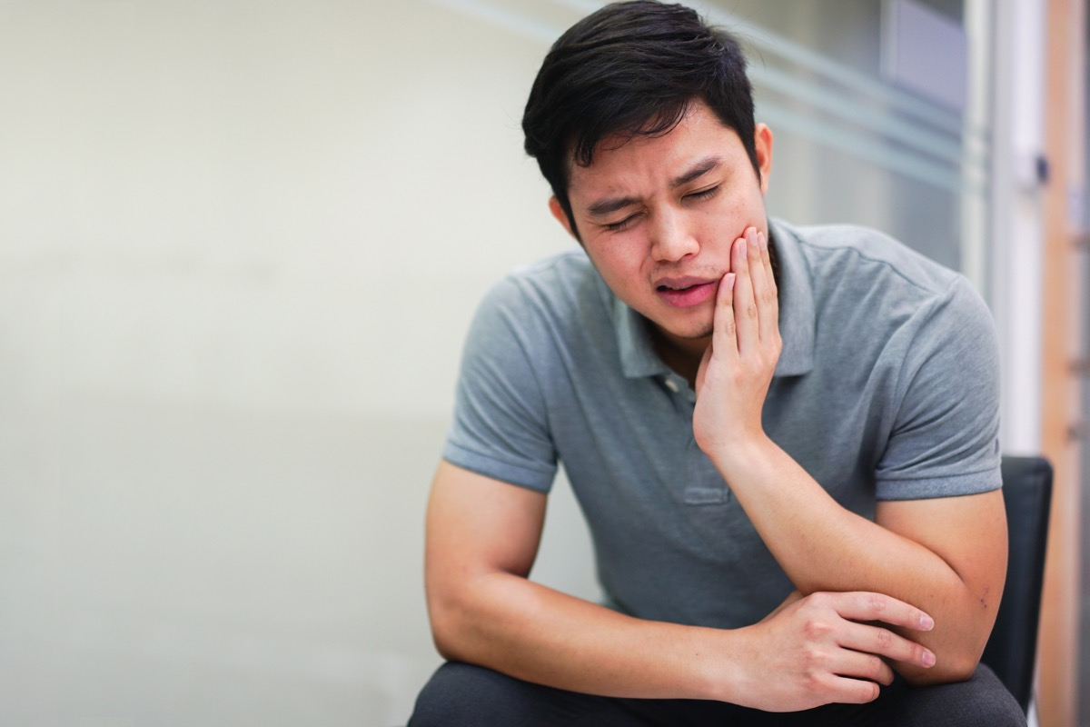 close up middle aged man feeling hurt from toothache symptom , unhealthy life concept