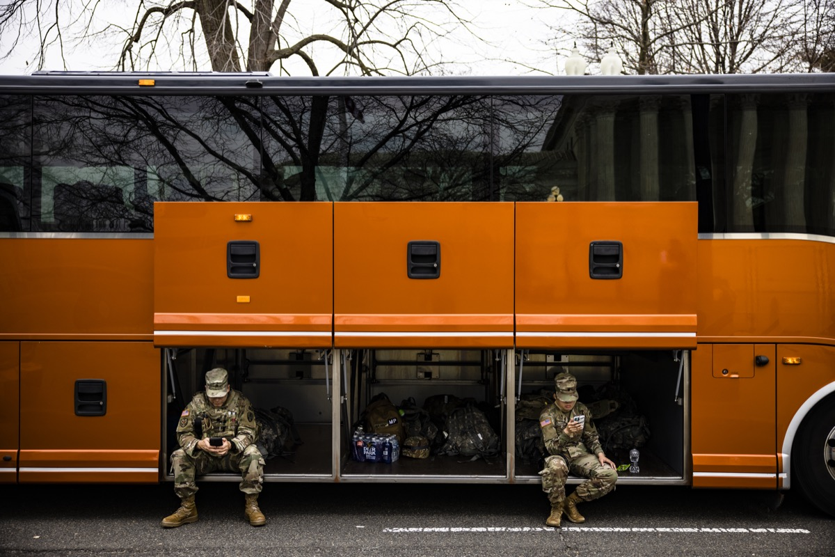 national guard members sitting in cargo hold of orange bus