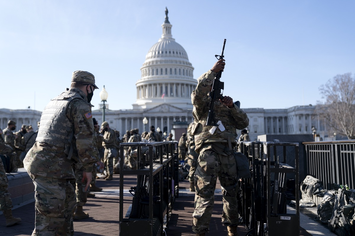 national guard member checks his rifle in front of capitol building