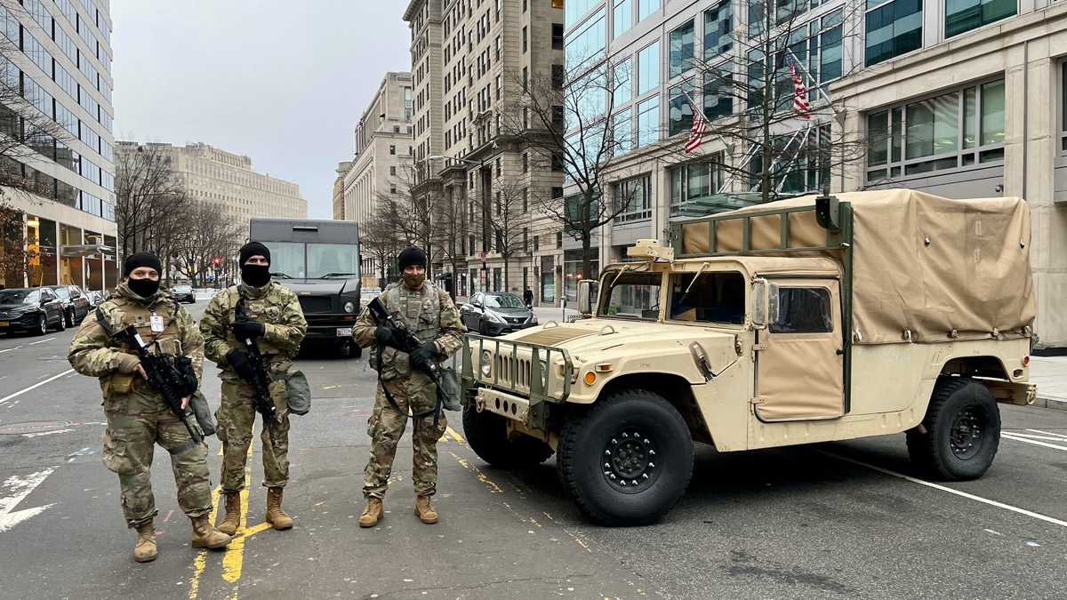 national guard members stand outside a military vehicle on a washington dc street