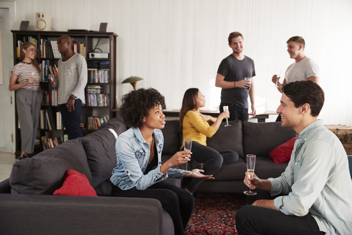A group of friends at a party in a New York loft apartment