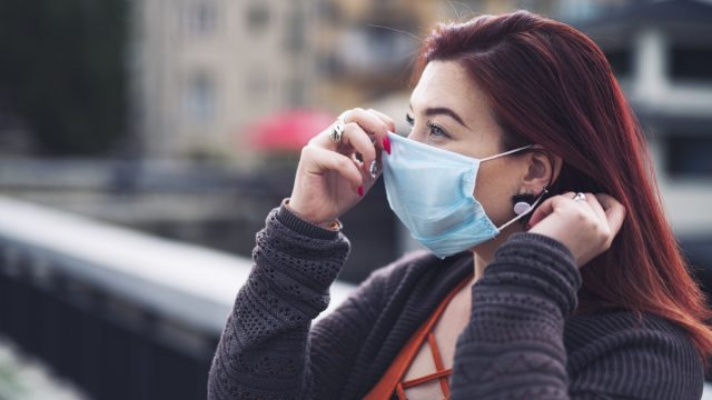 Side view of woman puts on protective face mask outdoor.