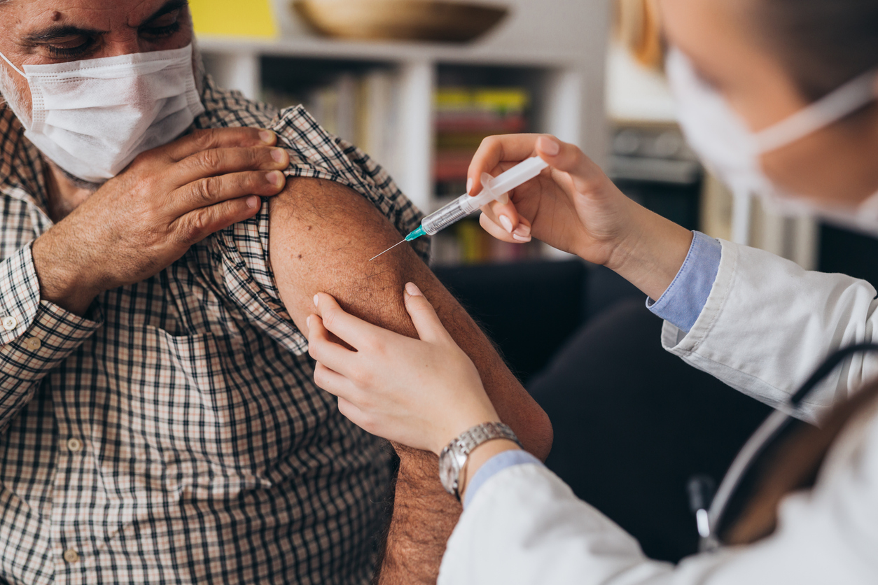 A senior man receives a COVID-19 vaccine injection in his arm from a healthcare worker.