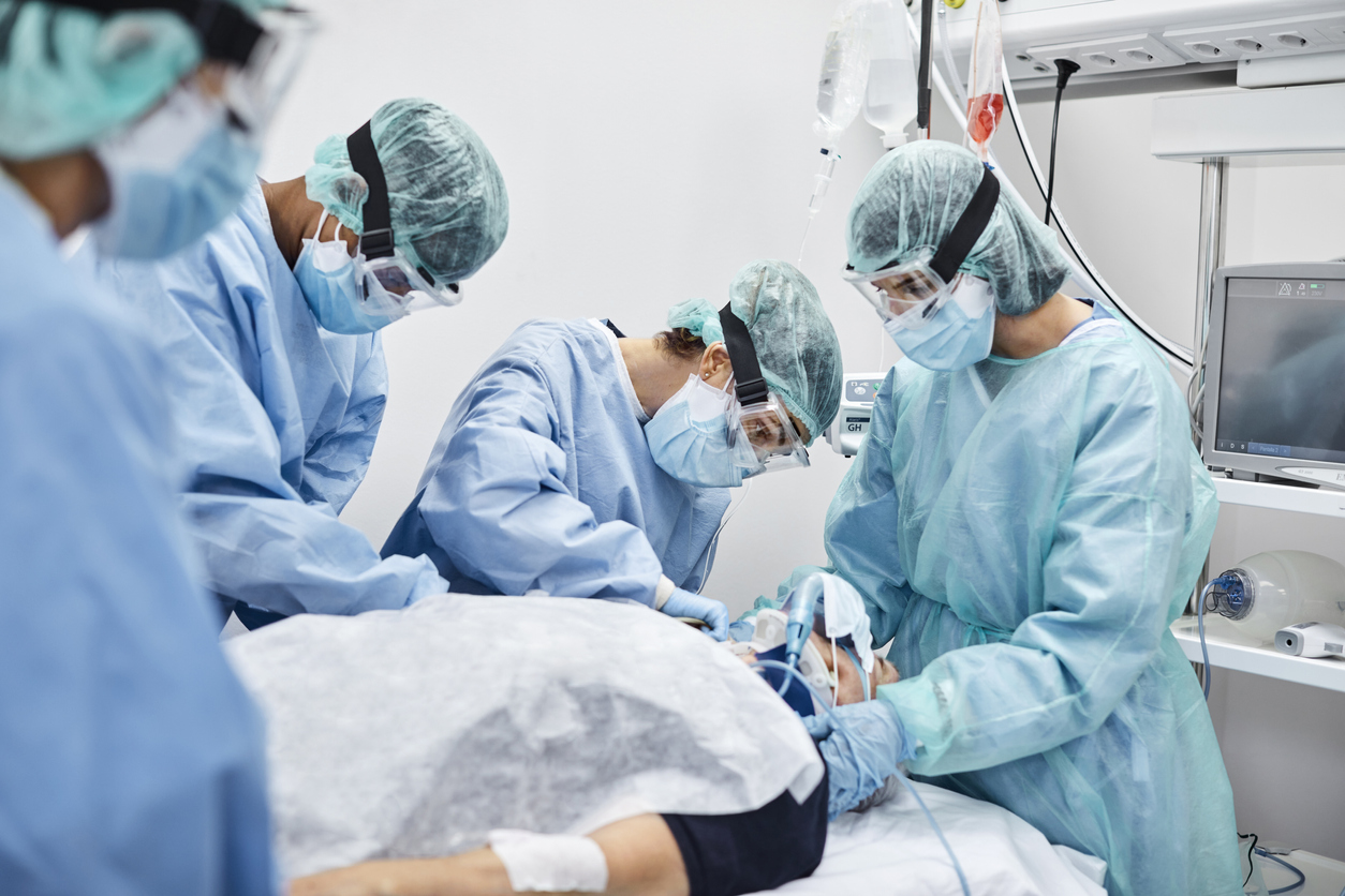 A patient suffering from COVID-19 is cared for by a team of doctors and nurses in the ICU who are all wearing protective gear.