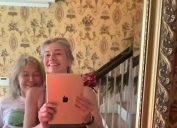 paulina porizkova and her mother showing their stomachs while taking a photo with an ipad in a mirror in a home
