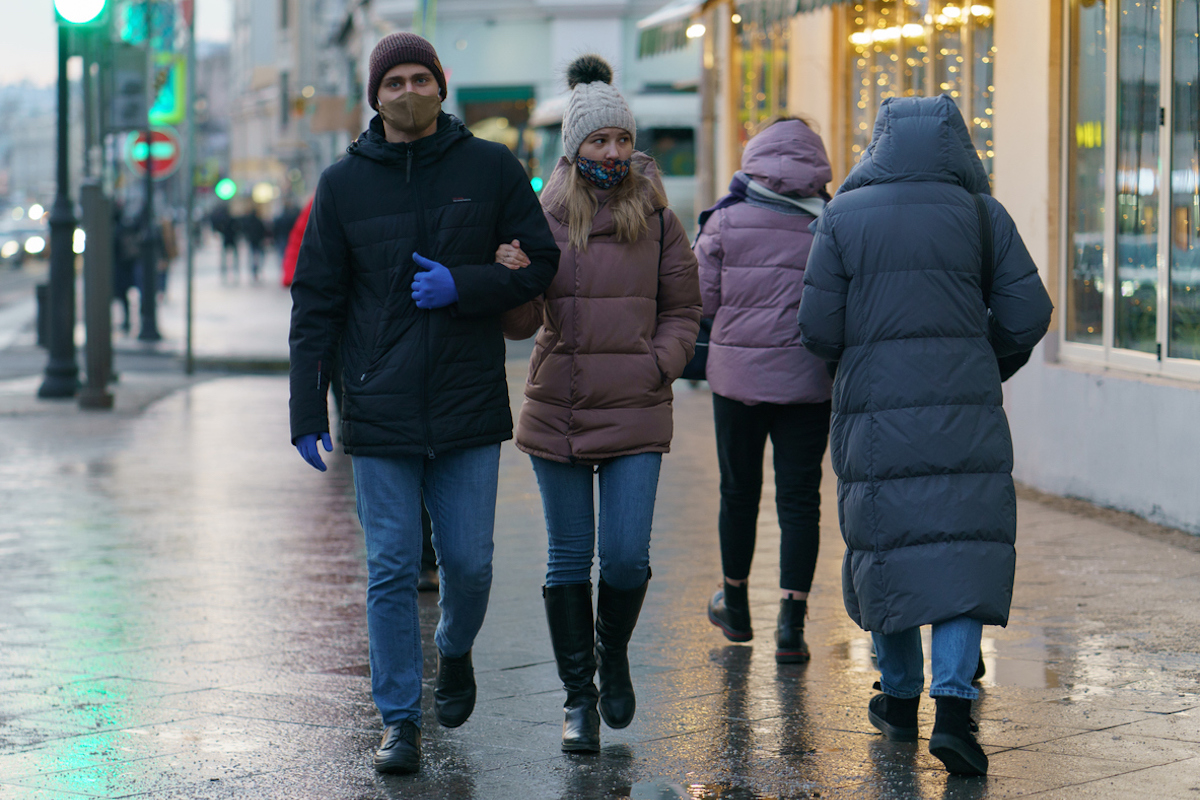 people wearing protective masks against COVID in city streets in winter