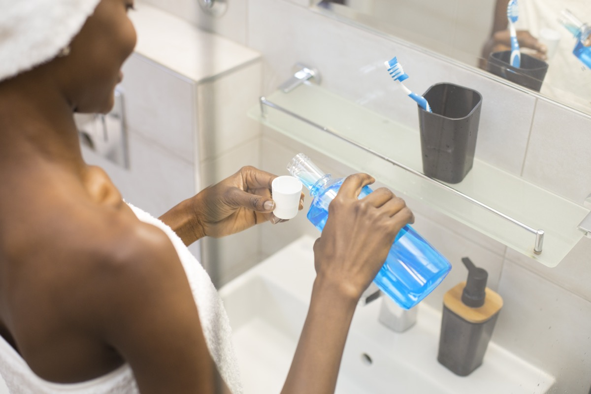 Young woman washing her teeth with mouthwash.