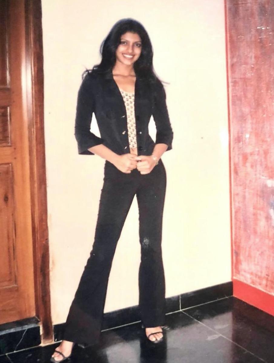 teenage priyanka chopra in a black bell bottom outfit standing against white wall