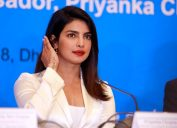 priyanka chopra in a white suit sitting at a desk