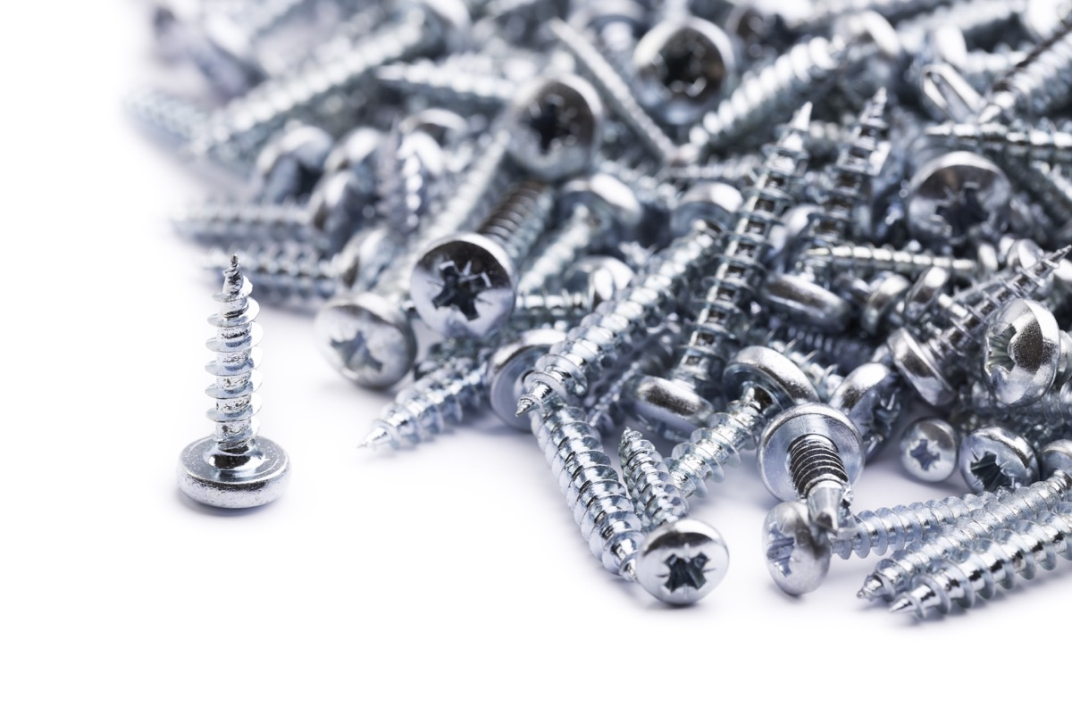 pile of steel nuts and bolts on white backgroundsee my