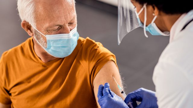 A senior man wearing a face mask receives a COVID-19 vaccine from a health care worker
