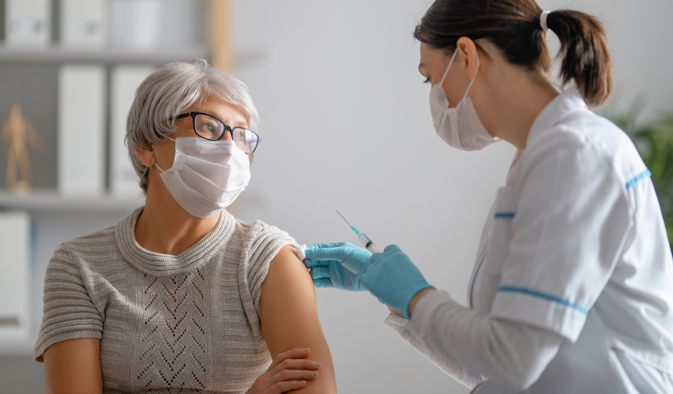 A senior woman wearing a face mask receives a COVID-19 vaccine from a female doctor.