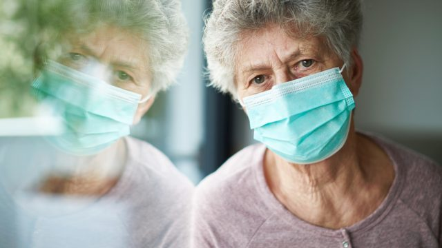 A senior woman wearing a face mask sits at a window with a distressed look on her face.