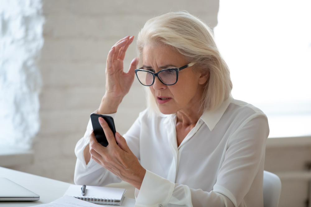 A senior woman wearing glasses and sitting at a desk looks at her smartphone with a surprised and confused look, maybe the victim of a scam.