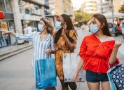 Three cheerful young friends wearing protective face masks and shopping in the city on beautiful sunny day.