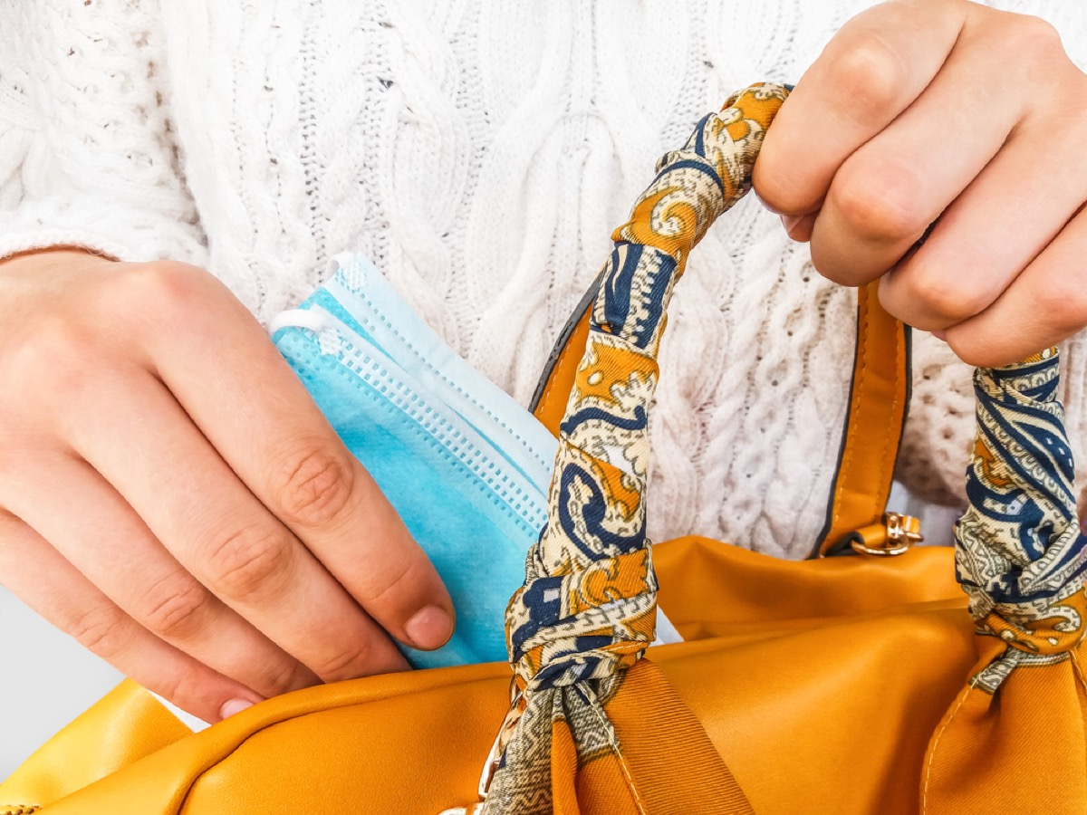 close up of hands putting face mask in purse