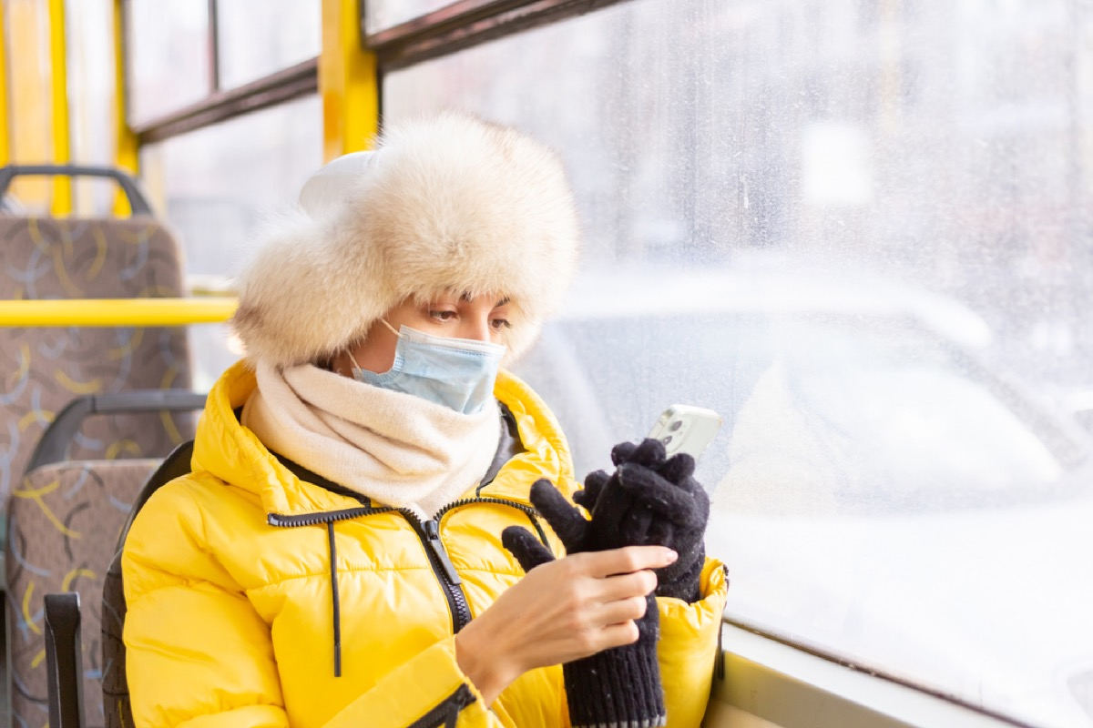woman in winter clothing with face mask on a bus looking at her phone