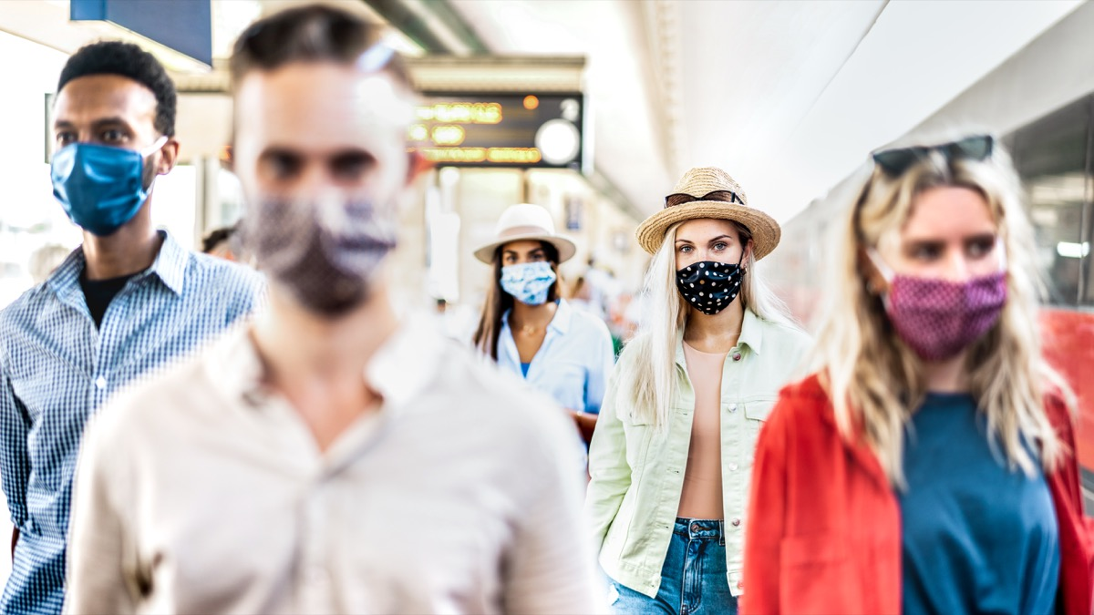 group walking with serious face expression at railway station - New normal travel concept with young people covered by protective mask - Focus on blond girl with hat