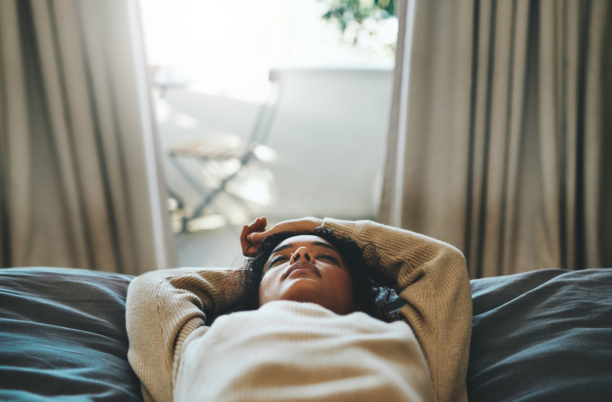 Cropped shot of a young woman lying on her bed with her eyes closed