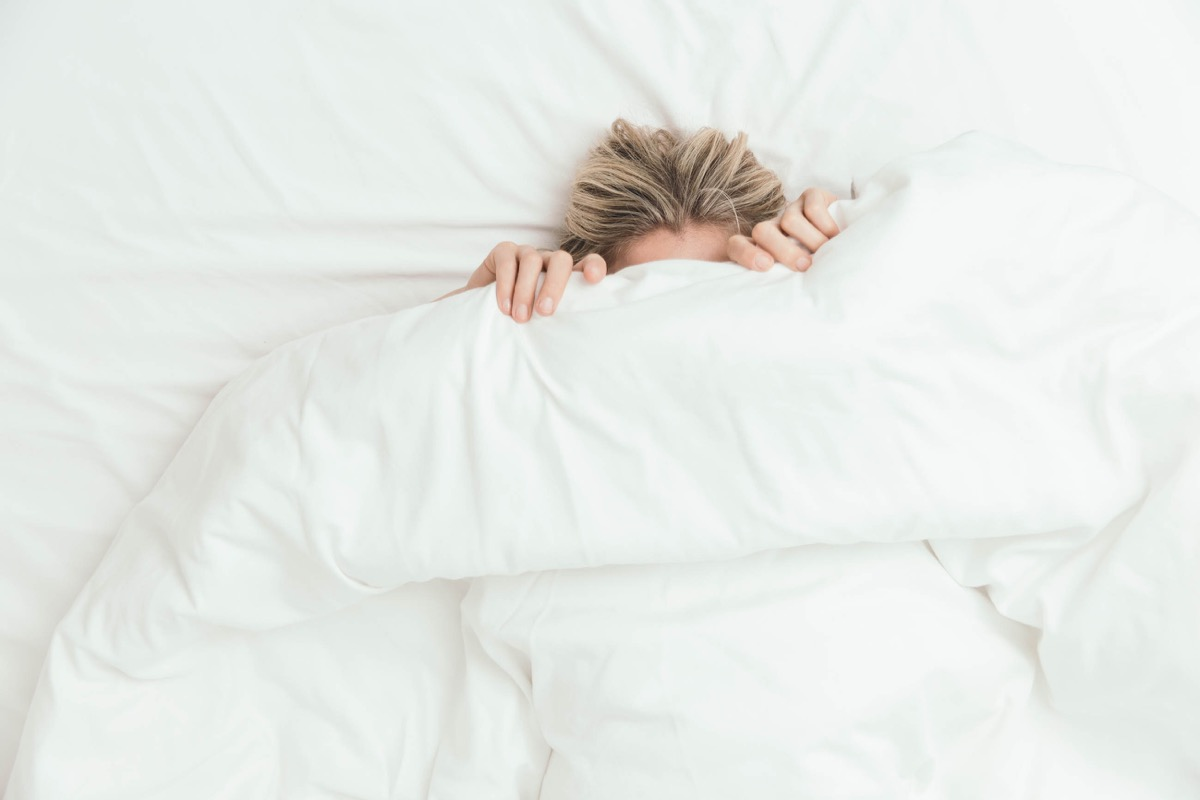 Woman in bed under covers