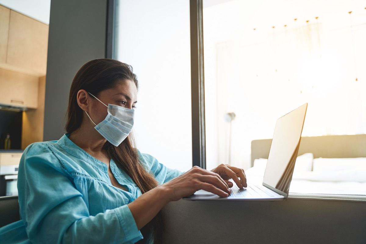 Focused serious dark-haired young female freelancer under quarantine working on her computer at home