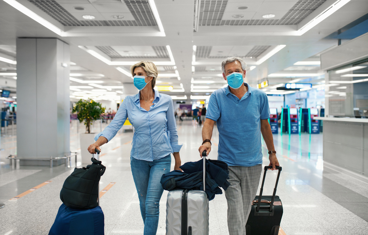 Closeup front view of a middle aged couple waiting for a flight amid coronavirus while wearing masks