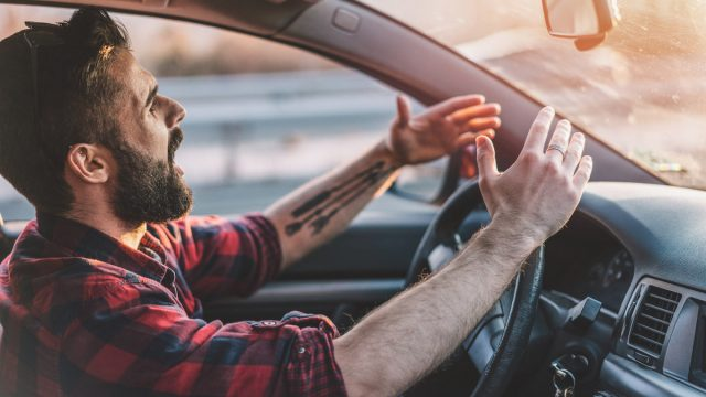 Side view image of irritated young man shouting at other drivers while driving on the highway