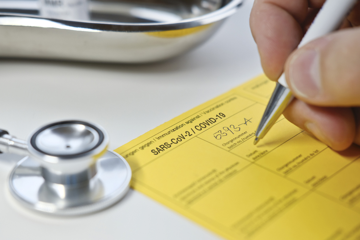 Doctor filling out yellow vaccination card for COVID vaccine