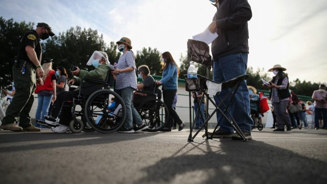 People wait in line to receive the COVID-19 vaccine at a mass vaccination site in a parking lot for Disneyland Resort on January 13, 2021 in Anaheim, California. California announced that effective immediately, all residents 65 or older are eligible to receive the vaccine