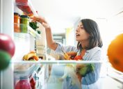 Shot from inside the fridge of a young woman picking some fruit and veggies from the fridge