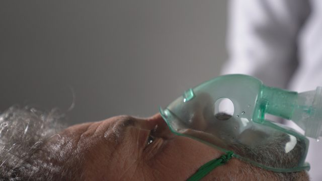 An old man infected by coronavirus is receiving ventilation in intensive care unit .