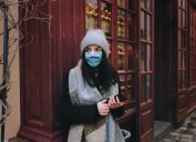Woman in a coat, a scarf, a hat and a protective medical blue mask is standing in street