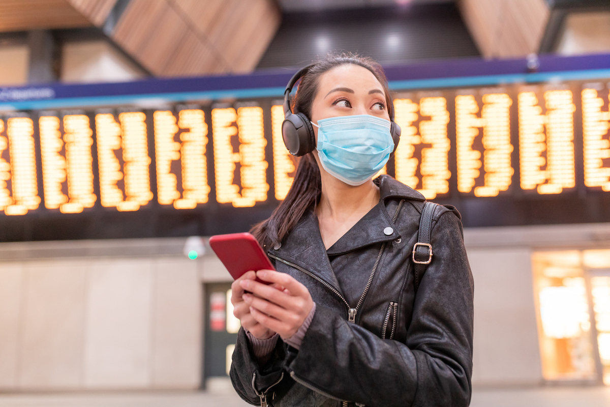 Woman wearing face mask at airport and maintaining social distance