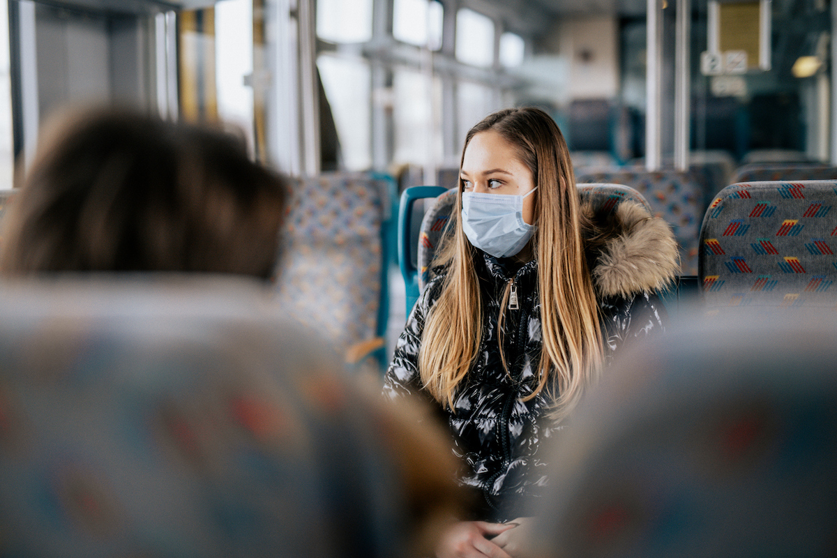 Young woman is wearing protective face mask while coronavirus is around. She is sitting on a bus or train. Photo is taken over the shoulder of another person. The woman in the main image is looking outside the window.